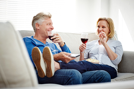 Happy mature couple watching television at home